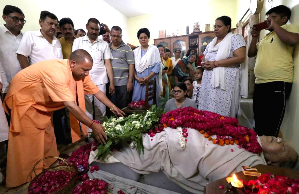 Lucknow: Uttar Pradesh Chief Minister Yogi Adityanath pays tributes to veteran journalist and former BJP MP Rajnath Singh Surya who passed away after a brief illness, at his Gomti Nagar residence in Lucknow on June 13, 2019. Singh had expressed a des - Yogi Adityanath and Rajnath Singh Surya
