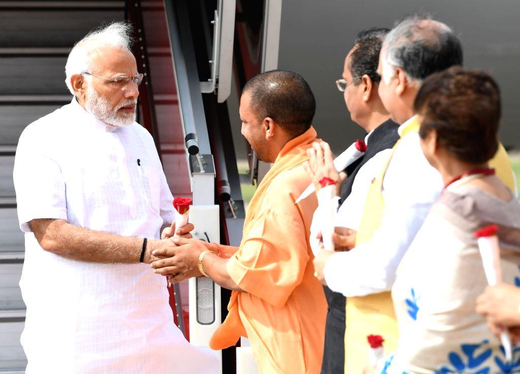 Lucknow: Uttar Pradesh Chief Minister Yogi Adityanath receives Prime Minister Narendra Modi on his arrival in Lucknow, Uttar Pradesh on June 28, 2018. (Photo: IANS/PIB) - Yogi Adityanath and Narendra Modi