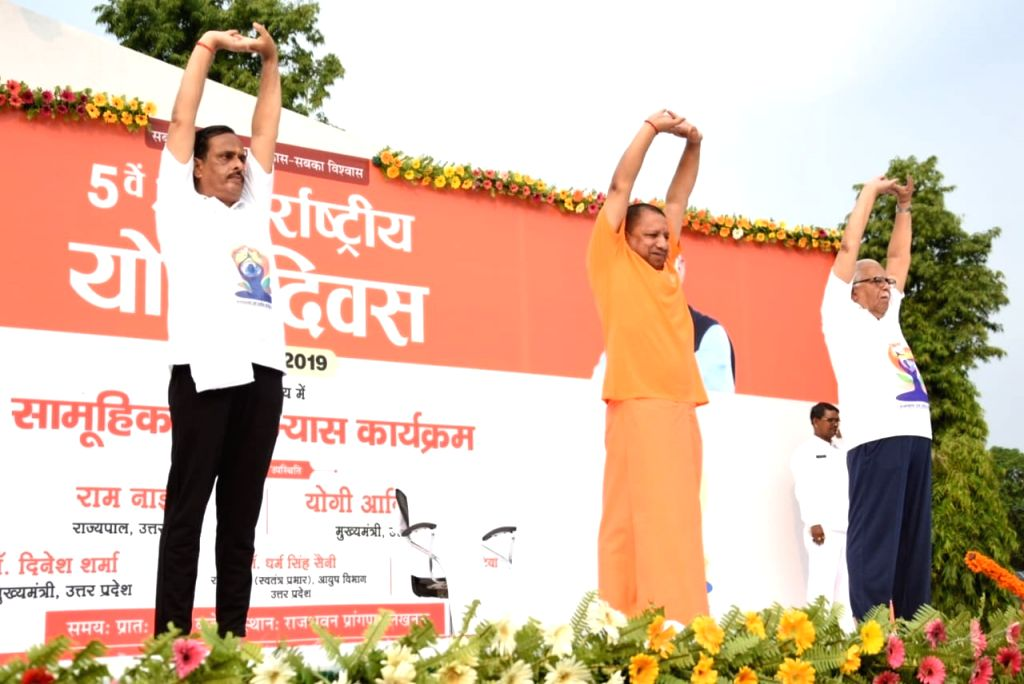 Lucknow: Uttar Pradesh Governor Ram Naik with Chief Minister Yogi Adityanath and Deputy Chief Minister Dinesh Sharma practice yoga asanas -postures- on International Yoga Day 2019 in Lucknow on June 21, 2019. (Photo: IANS) - Yogi Adityanath and Dinesh Sharma