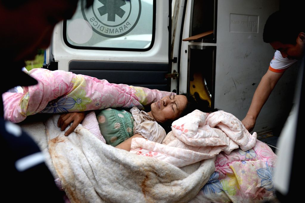 An injured woman is transferred in quake-hit southwest China's Yunnan Province, Aug. 4, 2014. At least 398 people have been killed after a 6.5-magnitude earthquake ...