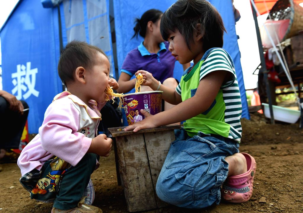 Xie Weijia (R), 5, and her sister have breakfast at a temporary resettlement in quake-hit Longtoushan Town of Ludian County, southwest China's Yunnan Province, Aug. ..