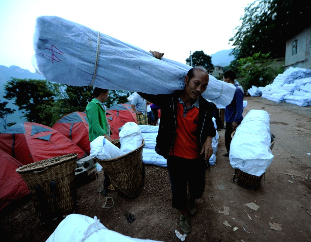 A man conveys relief materials in quake-hit Weigu Village of Qiaojia County, southwest China's Yunnan Province, Aug. 6, 2014.