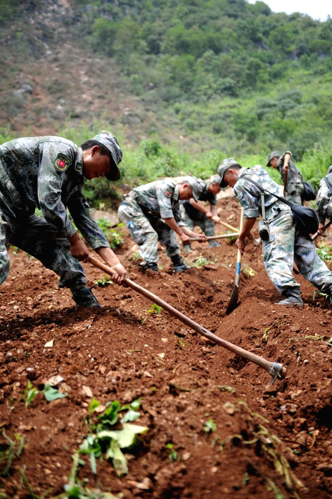 Rescuers dig a channel in quake-hit Pingdi Village of of Qiaojia County, southwest China's Yunnan Province, Aug. 7, 2014.