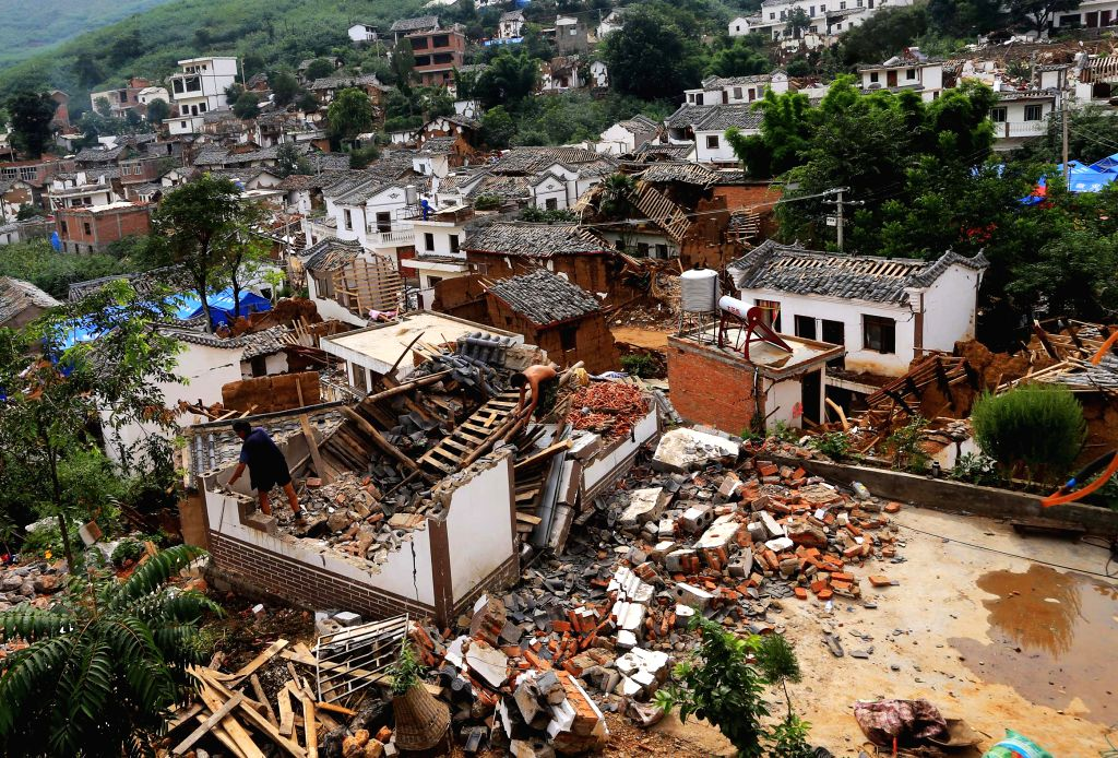 Villagers check their damaged houses in quake-hit Longtoushan Town of Ludian County, southwest China's Yunnan Province, Aug. 9, 2014.
