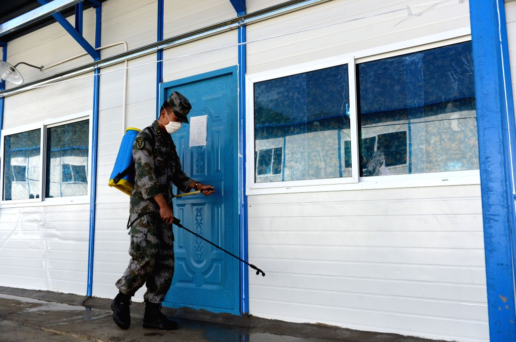 A soldier sprays disinfectant at the prefabricated school for students to have a clean campus in quake-hit Longtoushan Town of Ludian County, southwest China's ...