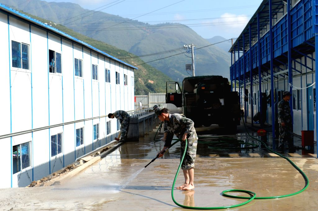 A soldier washes the muddy ground at the prefabricated school for students to have a clean campus in quake-hit Longtoushan Town of Ludian County, southwest China's ..