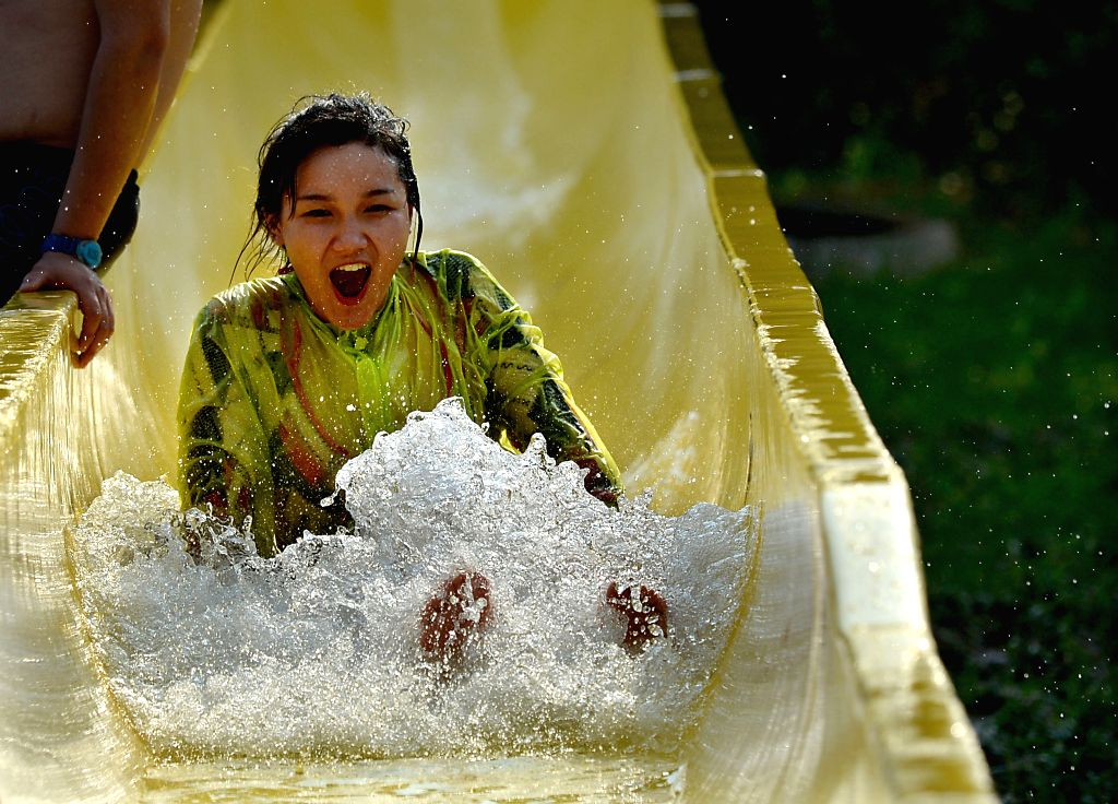 A woman slips down from a water slide at a water park in Luoyang, central China's Hunan Province, July 12, 2014. Lots of citizens and tourists spent the summer on ..
