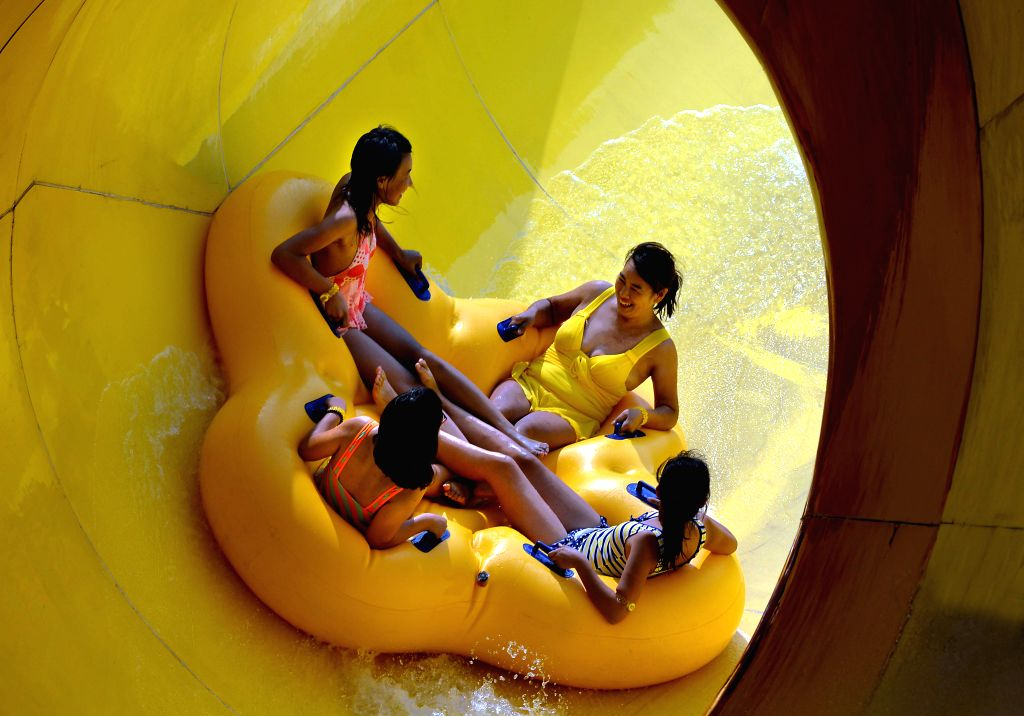 Citizens slip down from a water slide at a water park in Luoyang, central China's Hunan Province, July 12, 2014. Lots of citizens and tourists spent the summer on ..