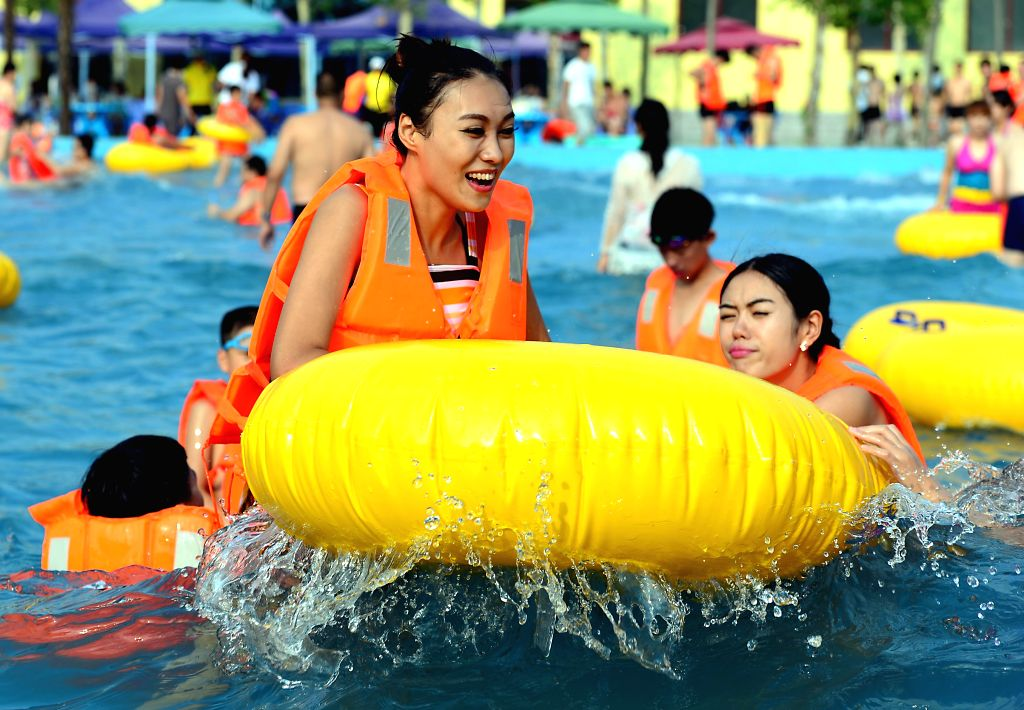 People have fun at a water park in Luoyang, central China's Hunan Province, July 12, 2014. Lots of citizens and tourists spent the summer on aquatic recreational ...