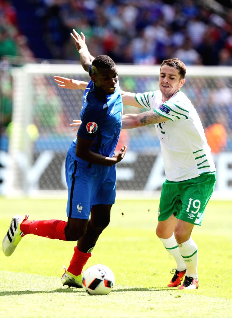 LYON, June 26, 2016 - France's Paul Pogba (L) and Ireland's Robbie Brady vie for the ball during the Euro 2016 round of 16 football match between France and Republic of Ireland in Lyon, France, June ...