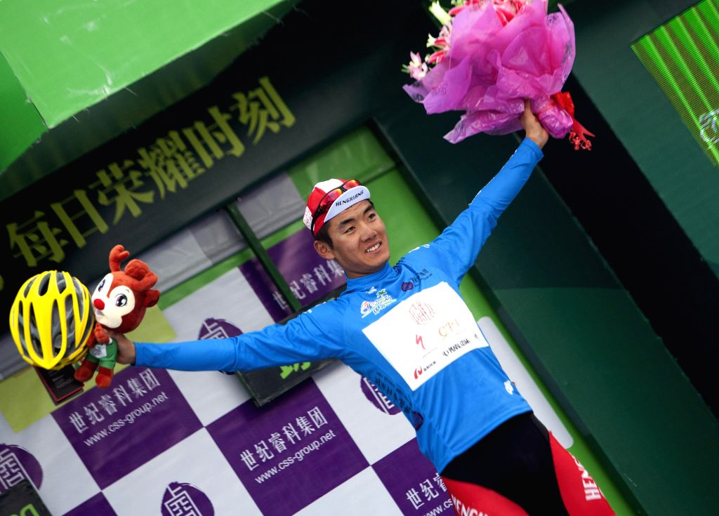 Ma Guangtong, who has got the blue jersey, celebrates during the awarding ceremony after the 5th stage of the 2015 Tour of Hainan International Road Cycling Race ...