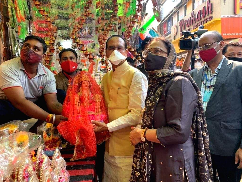 madhya pradesh chief minister shivraj singh chouhan wife sadhana singh ke sath maa laxmi ki murti lene new market bazar pahuche.