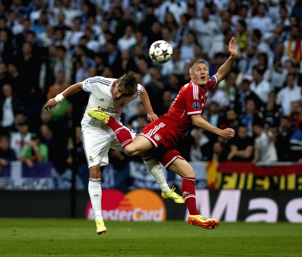 Real Madrid's Fabio Coentrao (L) vies with Bayern Munich's Bastian Schweinsteiger during their UEFA Champion League semi-final first leg soccer match in Madrid, ...