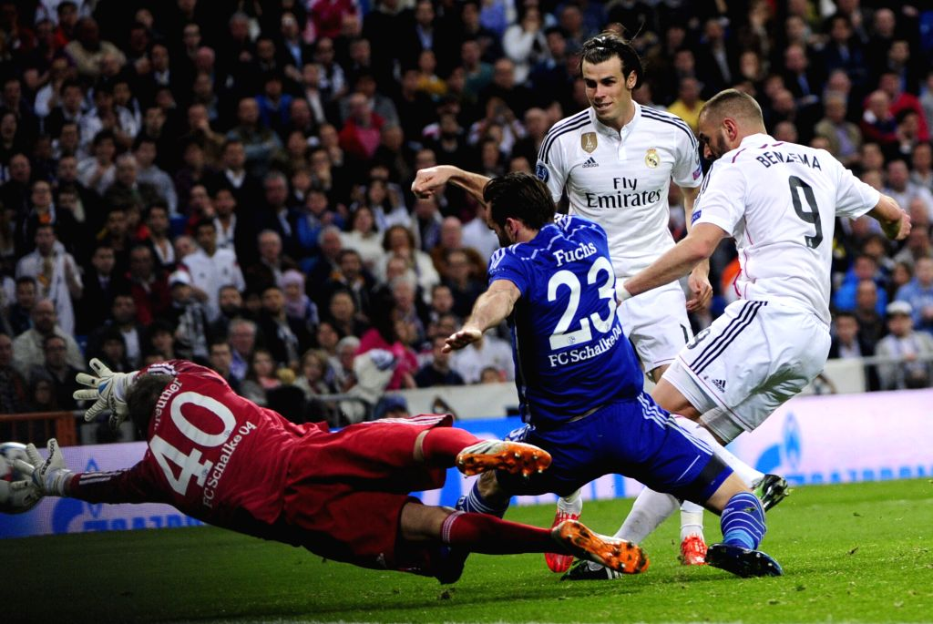 Real Madrid's French forward Karim Benzema (R) shoots the ball during the Champions League football match 2nd leg against Schalke 04 at Santiago Bernabeu Stadium in ...