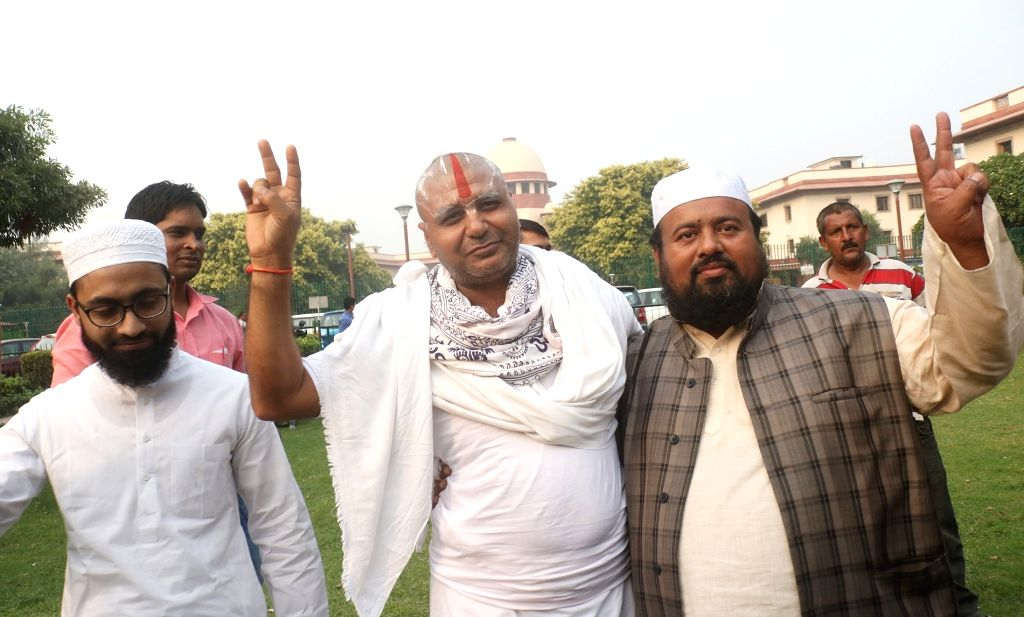 Mahant Ram Das of Nirmohi Akhara with Muslim litigants in the Ram Janmabhoomi-Babri Masjid dispute, outside the Supreme Court on the final day of hearing in the case, in New Delhi on Oct ...