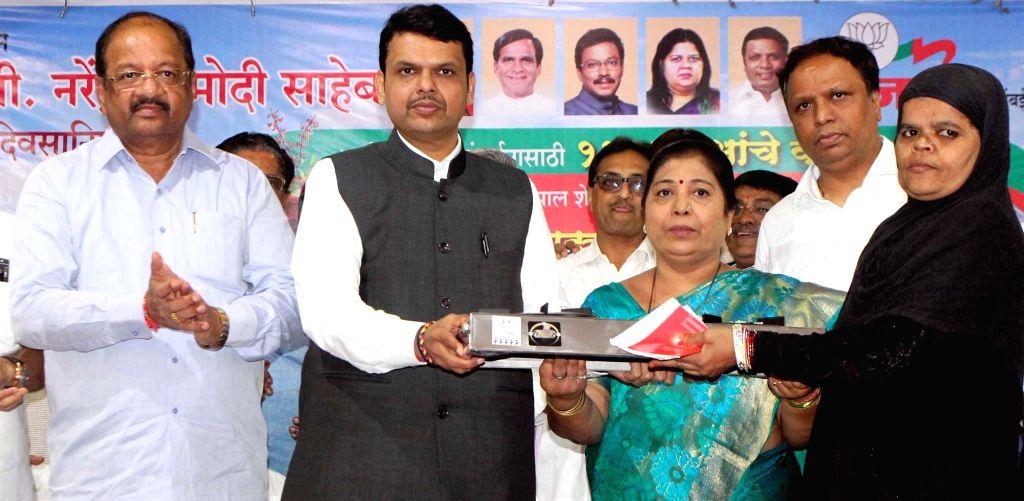 Maharashtra Chief Minister Devendra Fadnavis distributes Gas Stove to women in Mumbai, on Sept 18, 2016. - Devendra Fadnavis