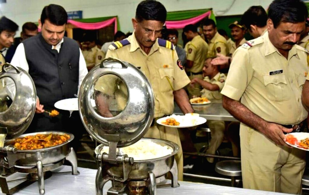 Maharashtra Chief Minister Devendra Fadnavis serves himself as he prepares to have lunch with police personnel at the state assembly, in Nagpur on July 14, 2018. - Devendra Fadnavis