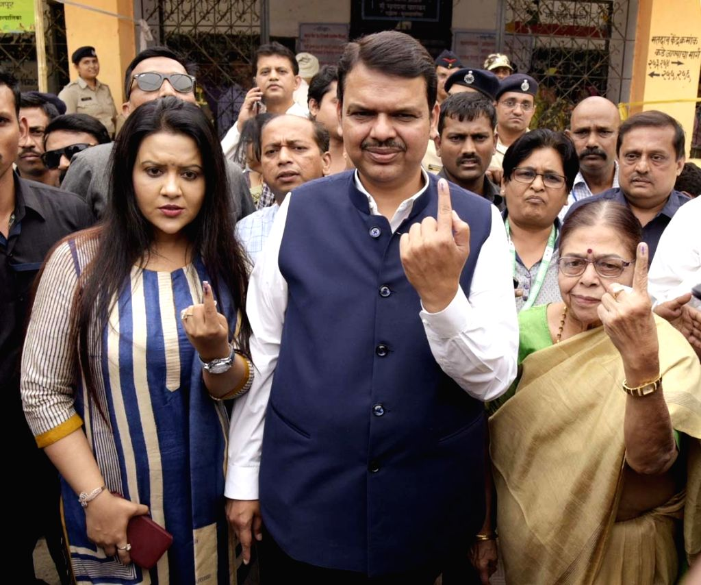 Maharashtra Chief Minister Devendra Fadnavis along with his family show their inked fingers after casting their votes during the first phase of ongoing 2019 Lok Sabha elections inNagpur on ... - Devendra Fadnavis