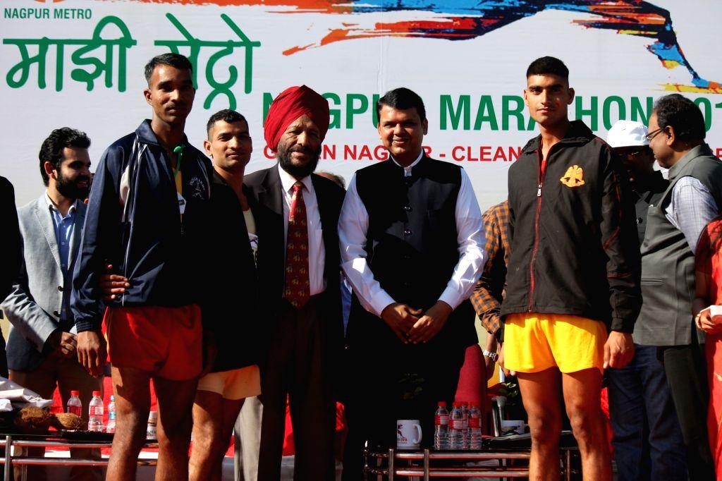 Maharashtra Chief Minister Devendra Fadnavis and legendary athlete Milkha Singh with the winners of Nagpur Marathon 2016 during prize distribution ceremony in Nagpur on Nov 27, 2016. - Devendra Fadnavis and Milkha Singh
