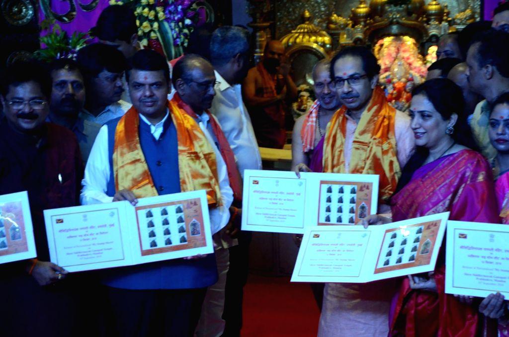 Maharashtra Chief Minister Devendra Fadnavis, Shiv Sena chief Uddhav Thackeray and his wife Rashmi Thackeray unveil stamps at Siddhivinayak Temple, in Mumbai on Sept 10, 2018. - Devendra Fadnavis