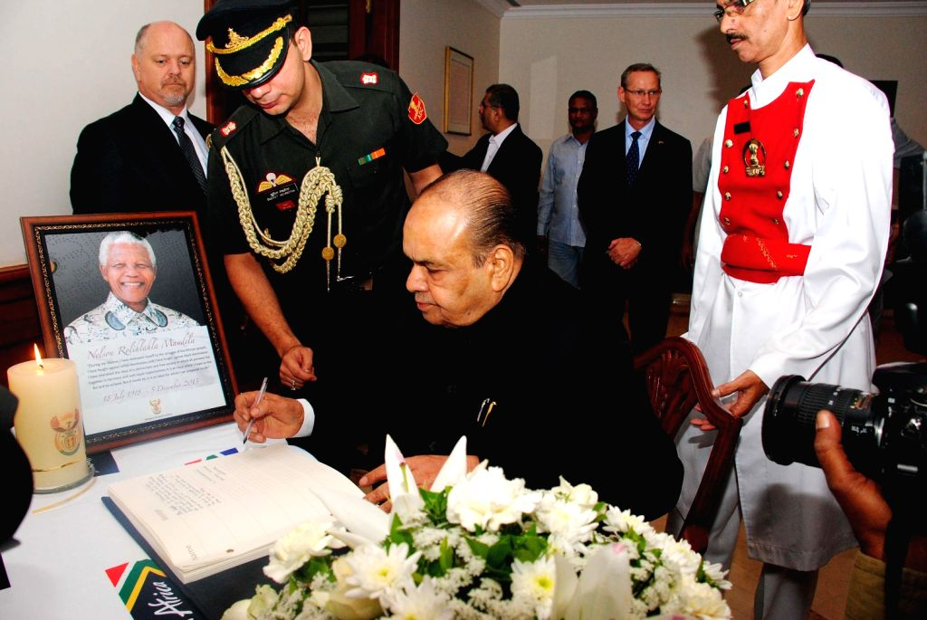 Maharashtra Governor K Sankaranarayanan pays tribute to South Africa's anti-apartheid icon Nelson Mandela who died on 5th Dec,  at Consulate Of South Africa in Mumbai on Dec.13, 2013. (Photo: ...
