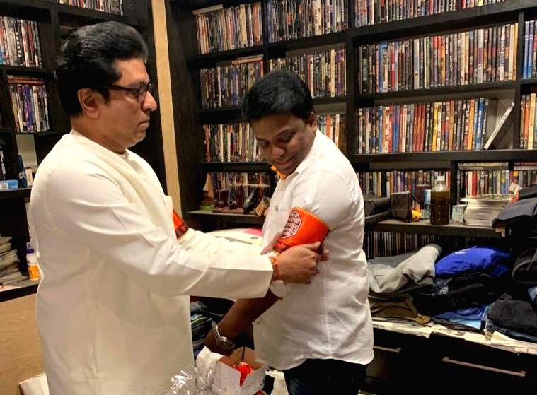 Maharashtra Navnirman Sena (MNS) President Raj Thackeray ties the party flag arm-band to a party member before commencing his mega-morcha demanding that Pakistan-Bangladesh infiltrators must ...
