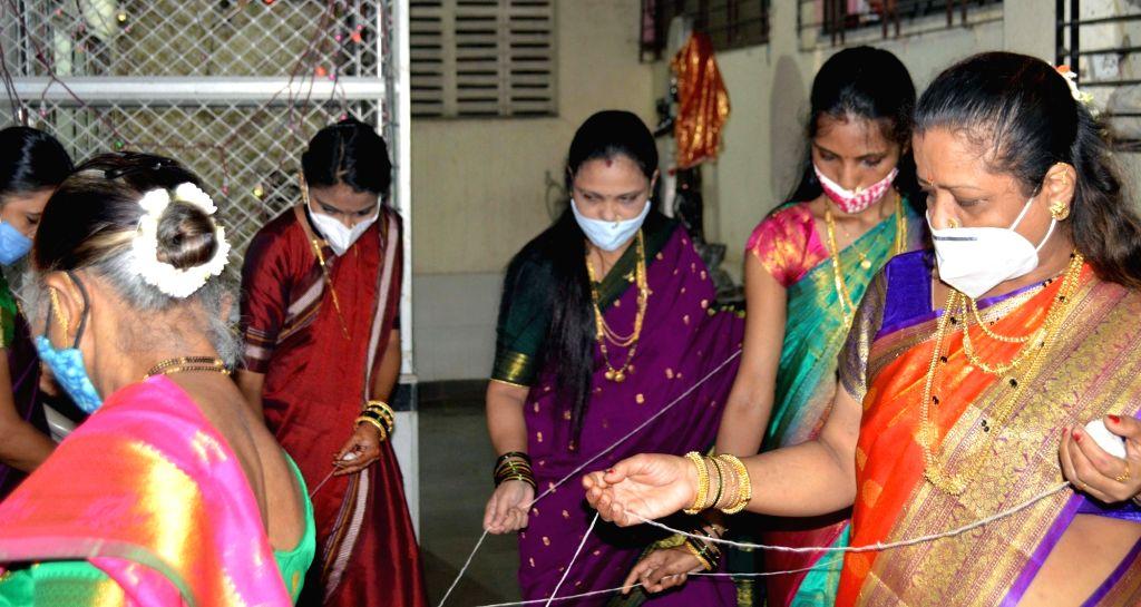 Mahashtrian womens offering prayer to Banyan Tree at Prabhadevi during traditional Vat Purnima Celebration in Mumbai on Thursday, June 24, 2021. (Photo : Sandeep Mahankal/ IANS)