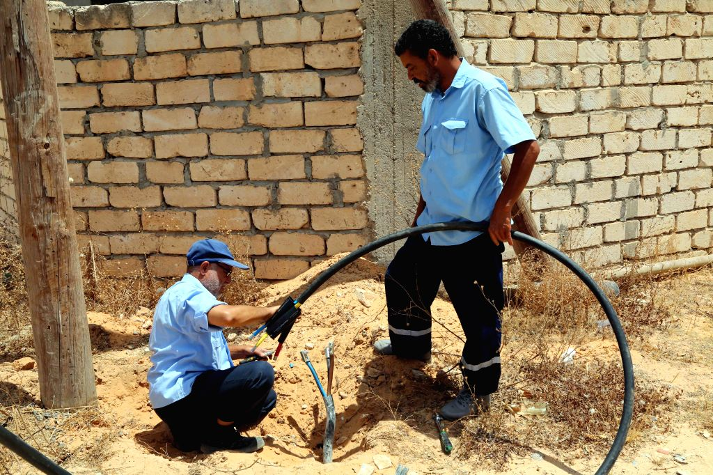 Maintenance workers from Libyan Electricity Company repair a line in Salah al-Din area, southern Tripoli, Libya, on June 23, 2020. Most Libyan cities, especially ...