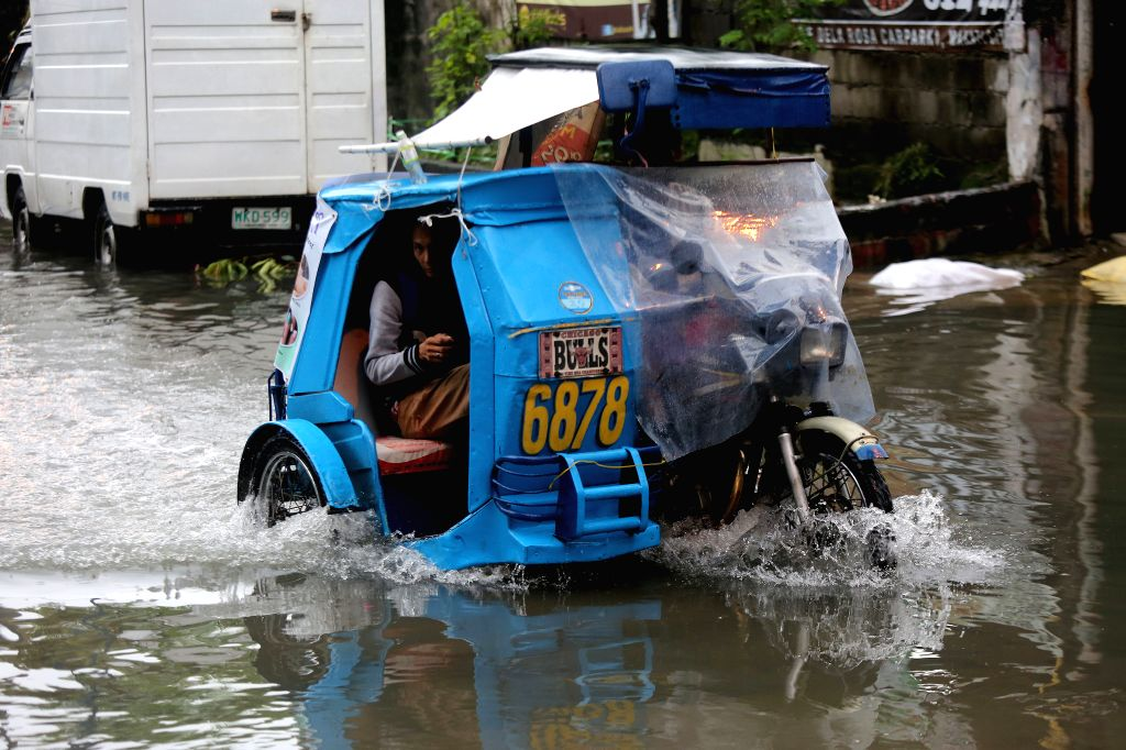 MAKATI CITY, Aug. 14, 2016 - A rickshaw wades through the floodwaters brought by the monsoon rains in Makati City, the Philippines, Aug. 14, 2016. At least five people were killed and over 70,000 ...
