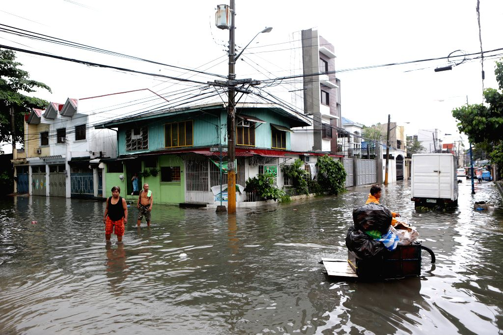 MAKATI CITY, Aug. 14, 2016 - Residents wade through the floodwaters brought by the monsoon rains in Makati City, the Philippines, Aug. 14, 2016. At least five people were killed and over 70,000 ...