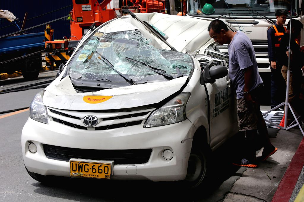 MAKATI CITY, May 26, 2016 - A man looks at the wreckage of a taxi after a construction crane collapsed on a street in Makati City, the Philippines, May 26, 2016. The construction crane collapsed on ...