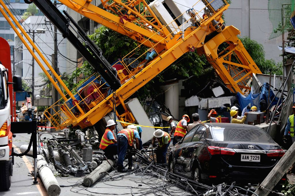 MAKATI CITY, May 26, 2016 - Workers clear the debris after a construction crane collapsed on a street in Makati City, the Philippines, May 26, 2016. The construction crane collapsed on several ...