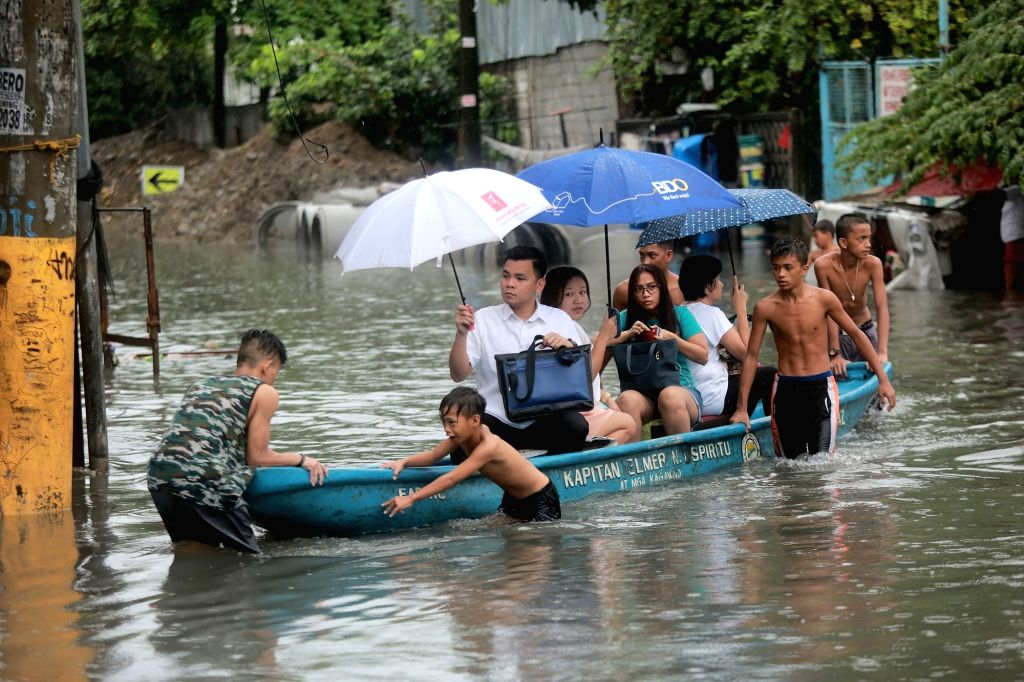 MAKATI CITY, Sept. 12, 2017 - Residents use a plastic boat to wade through floodwaters in Makati City, the Philippines, on Sept. 12, 2017. Floods caused by a tropical storm submerged many streets and ...