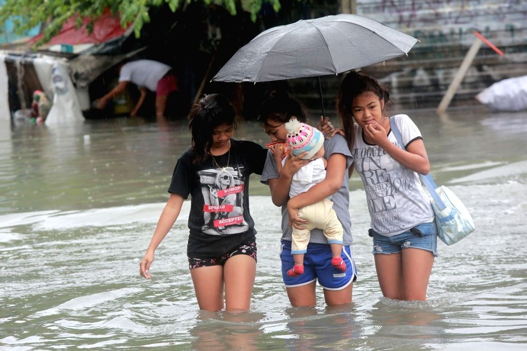 MAKATI CITY, Sept. 12, 2017 - Residents wade through flood in Makati City, the Philippines, on Sept. 12, 2017. Floods caused by a tropical storm submerged many streets and highways in the Philippines ...