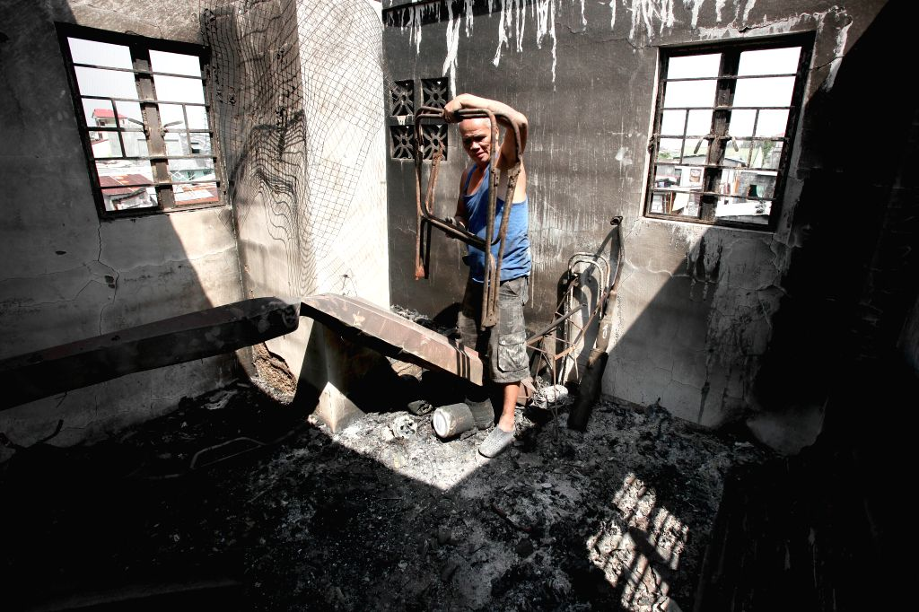 A resident searches for his belongings from burnt houses after a fire at a slum area in Malabon City, the Philippines, March 18, 2015. Seven people were ...
