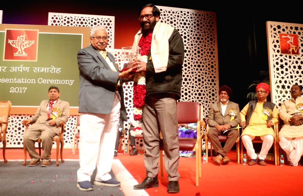 Malayalam novelist and short story writer K.P. Ramanunni being awarded by Sahitya Akademi Vice President Chandrashekhara Kambar during the Sahitya Akademi Awards in New Delhi on Feb 12, ...