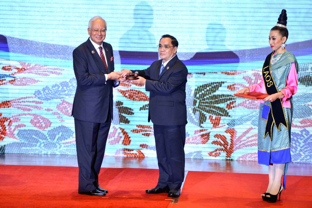 Malaysian Prime Minister Najib Razak (L) hands over the ASEAN chairmanship to Laos Prime Minister Thongsing Thammavong (C) during the closing ceremony of the ... - Najib Razak