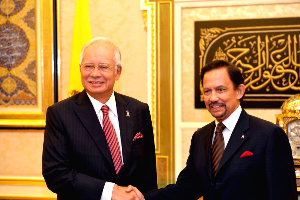 Malaysian Prime Minister Najib Razak (L) shakes hands with Brunei's Sultan Haji Hassanal Bolkiah during the 19th Annual Leaders' Consultation at Istana ... - Najib Razak