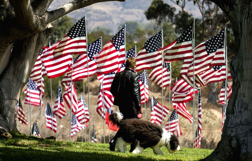 MALIBU, Sept. 11, 2018 - A man walks his dog among U.S. national flags erected to honor the victims of the September 11, 2001 attacks in New York, at the campus of Pepperdine University in Malibu, ...