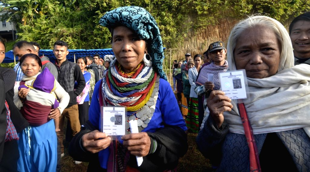 Mamit: Reang tribal refugees, sheltered in Tripura for the past 21 years, show their Voter ID cards as they arrive to cast their votes for Mizoram Assembly elections in Mamit district of Mizoram, on Nov 28, 2018. (Photo: IANS)