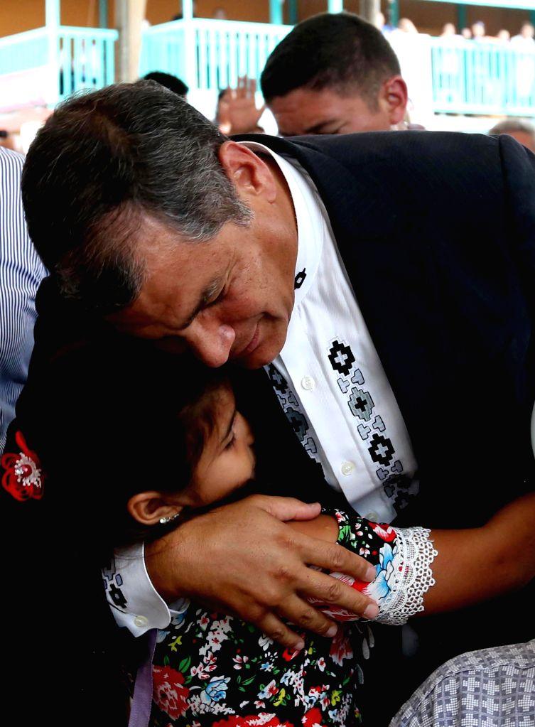 MANABI, April 17, 2017 - Ecuadorian President Rafael Correa hugs a girl during an open-air mass in the town of Pedernales, Manabi province, Ecuador, on April 16, 2017. Ecuador held an open-air mass ...