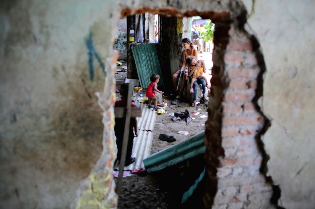 A woman and her children stay inside an affected structure after Sunday's earthquake in Managua, capital of Nicaragua, on April 14, 2014. Two earthquakes, ...