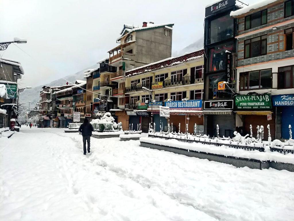 Manali: A man walks through a snow-covered road after heavy snowfall in Manali, Himachal Pradesh on Jan 23, 2019. (Photo: IANS)