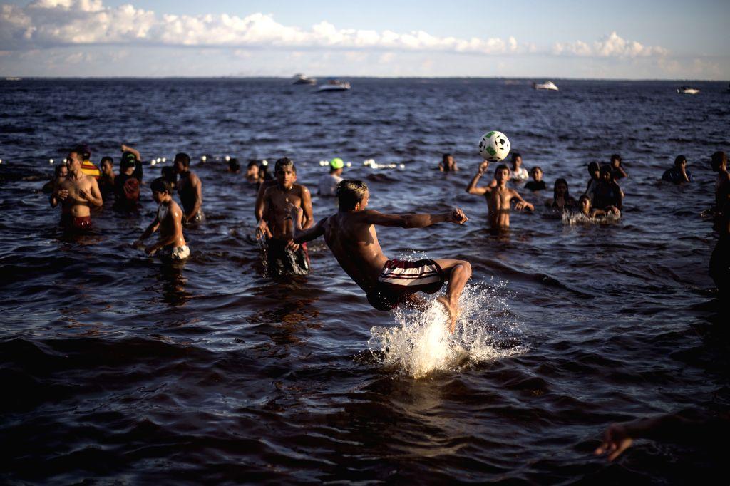 Brazilians play football in the sea near a beach in Ponta Negra in Manaus, Brazil, on June 15, 2014.