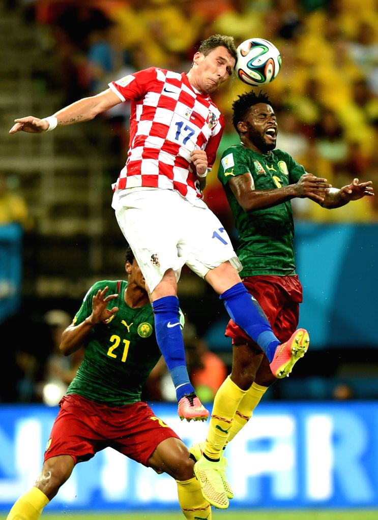 Croatia's Mario Mandzukic competes for a header with Alexandre Song during a Group A match between Cameroon and Croatia of 2014 FIFA World Cup at the Arena Amazonia .