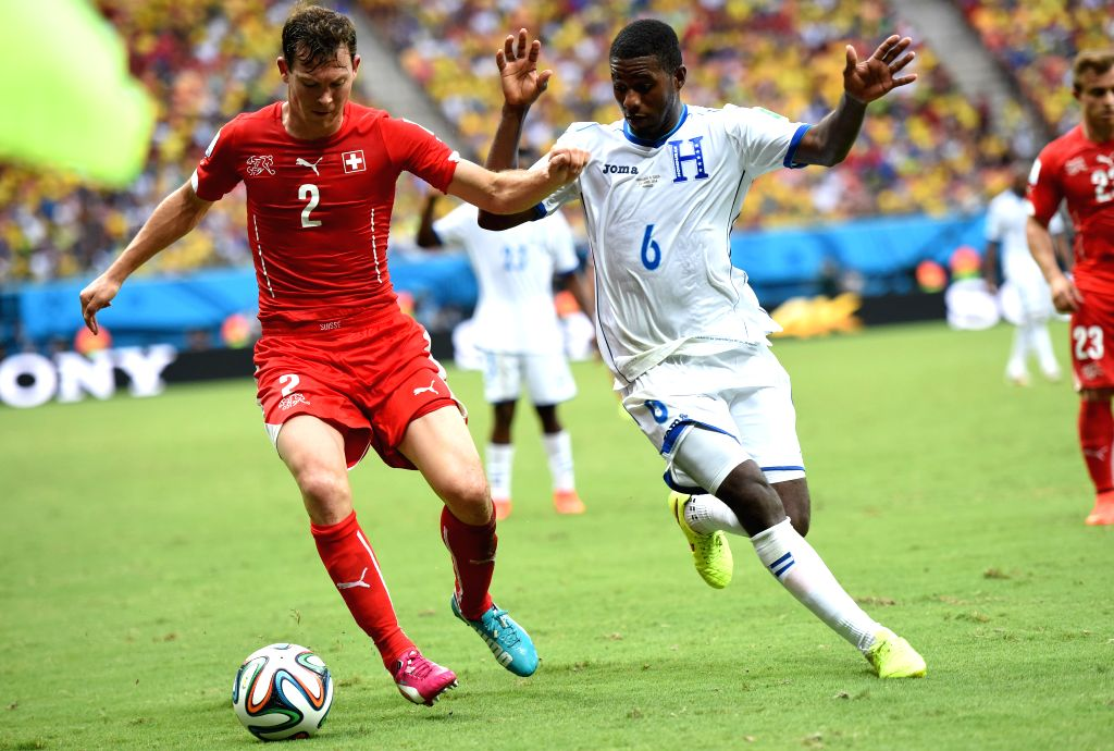 Switzerland's Stephan Lichtsteiner (L, front) vies with Honduras' Juan Carlos Garcia during a Group E match between Honduras and Switzerland of 2014 FIFA World Cup ..