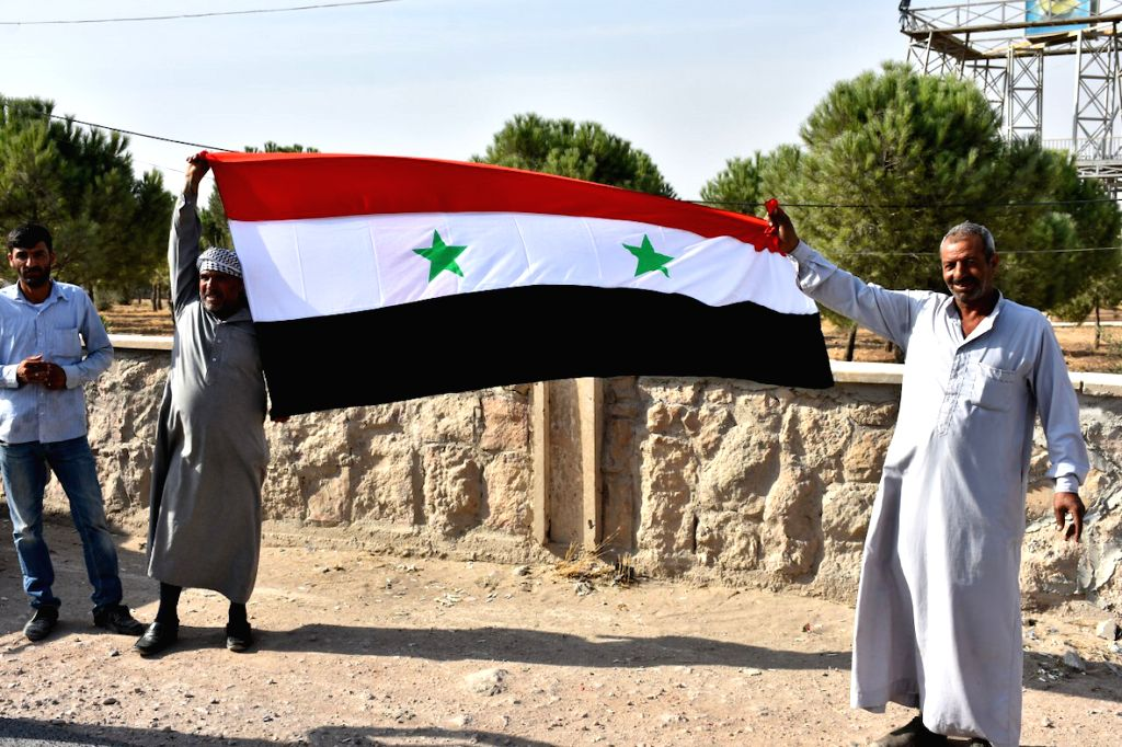 MANBIJ, Oct. 16, 2019 - Syrians hold a national flag during a celebration for the entry of the Syrian army into the city of Manbij in northern Syria on Oct. 15, 2019. The Syrian army assumed full ...
