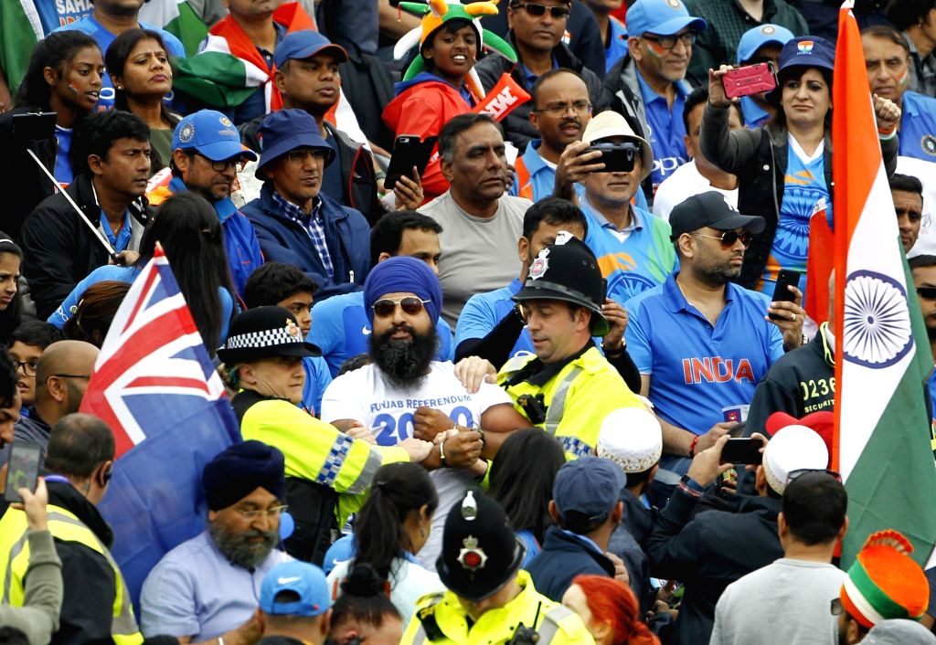 Manchester: A handcuffed Sikh spectator (C) reacts after being taken away by police personnel during the 1st Semi-final match of 2019 World Cup between India and New Zealand at Old Trafford in Manchester, England on July 9, 2019. (Photo: Surjeet Kuma - Surjeet Kumar