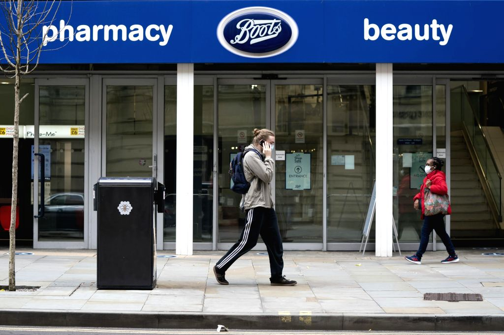 MANCHESTER (BRITAIN), July 9, 2020 People walk past a Boots store in Manchester, Britain, on July 9, 2020. British high street pharmacy chain Boots announced Thursday that it will cut ...