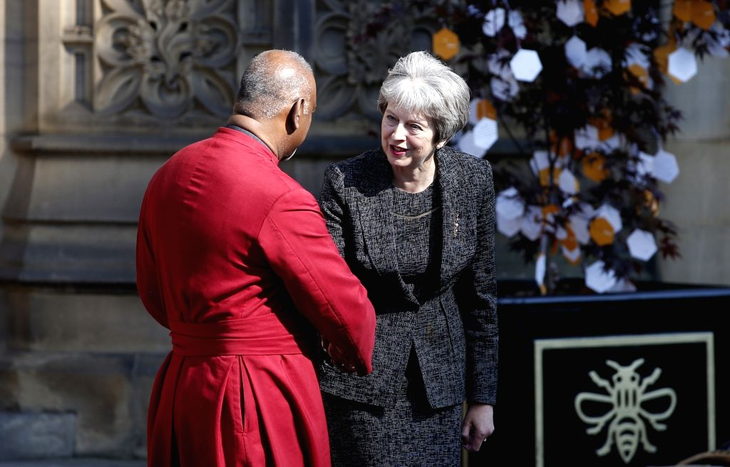 MANCHESTER (BRITAIN), May 22, 2018 British Prime Minister Theresa May (R) shakes hands with the Dean of Manchester Rogers Govender as she leaves Manchester Cathedral after the national ... - Theresa May